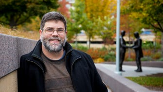 """Jeff Suess, The Enquirer's librarian, poses for a portrait at Smale Riverfront Park near the statue honoring the black brigade Tuesday, November 22, 2016. The story of those soldiers is a part of his latest book, """"Hidden History."""""""