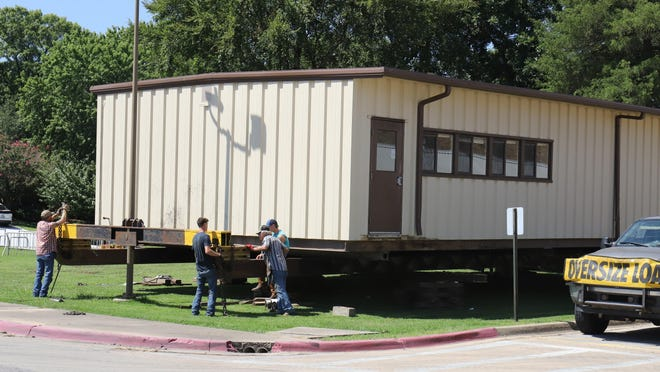 Workers with Combs House Movers relocate a portable building from Southside High School to Cook Elementary School, Thursday, Aug. 20, 2020, to be used a temporary library as the school prepares for the start of the 2020-2021 school year.