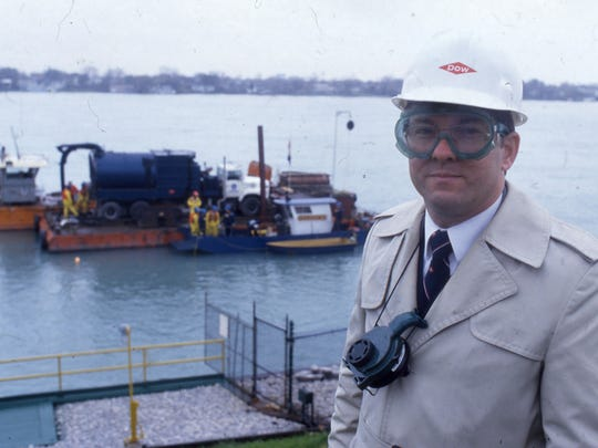 A Dow official stands in front of a vacuum truck loaded onto a barge in November 1985 to cleanup a blob of chemical spills on the St. Clair River.