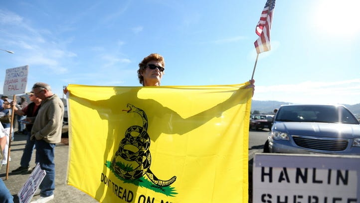 """Leslie Corp, 62, of Wolf Creek, holds a """"Don't Tread"""