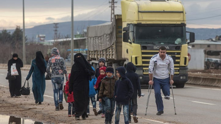 A truck arriving at the border passes people walking toward a temporary housing complex located at the closed Turkish border gate on Feb. 7, 2016 in Kilis, Turkey. According to Turkish officials some 35,000 Syrian refugees have massed on the Syrian/Turkish border after fleeing Russian airstrikes and a regime offensive surrounding the city of Aleppo in northern Syria.