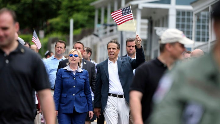 New York Gov. Andrew Cuomo waves a American flag as he walks with Hillary Clinton in a Memorial Day parade on May 30, 2016, in Chappaqua.