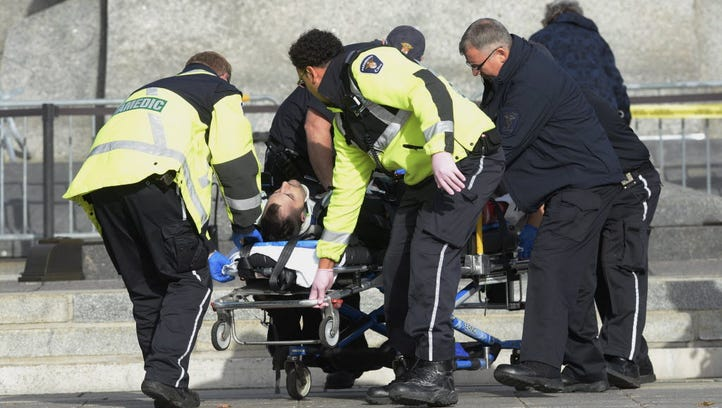 Paramedics and police wheel away a shooting victim