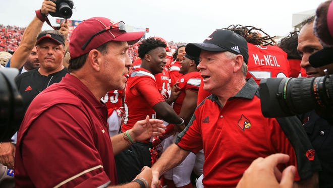 Florida State's Jimbo Fisher shakes the hand of Louisville's Bobby Petrino after the Cardinals routed the Seminoles 63-20 Saturday afternoon.