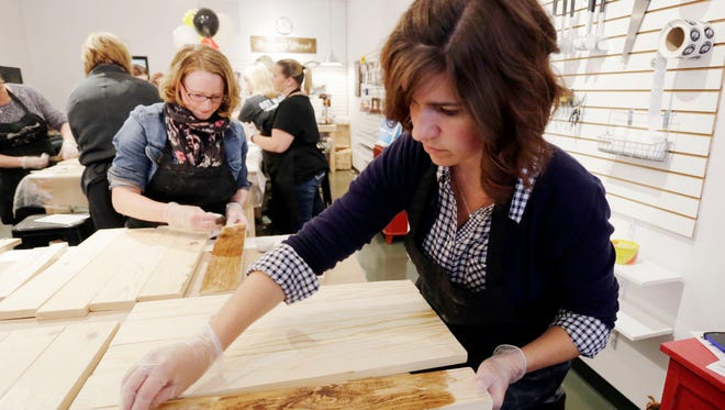 Lisa Fritchen of Sheboygan begins to stain a board for her sign project at Board and Brush Creative Studio Thursday April 28, 2016 in Sheboygan.