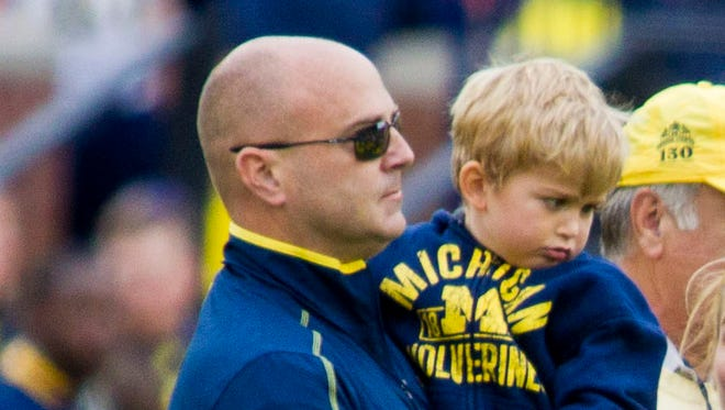 Jason Carr holds son Chad on the Michigan Stadium in Ann Arbor on Sept. 12, 2015.