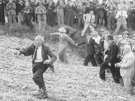 "Soviet Premier Nikita Khrushchev, far right, smiles as Roswell ""Bob"" Garst, irked by a crush of reporters and photographers, tosses silage at them. Khrushchev visited Garst's Coon Rapids farm on Sept. 23, 1959."
