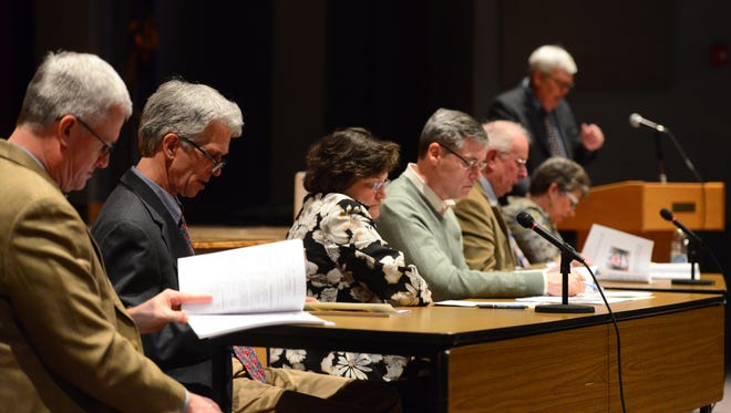 Williston officials thumb through the annual town report Monday night at Williston Central School.