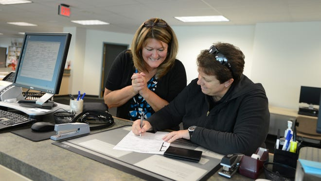 Barb Cooney (left) and Lisa Hill apply for a marriage license at the Marion County Clerk's Office in downtown Salem on Monday.