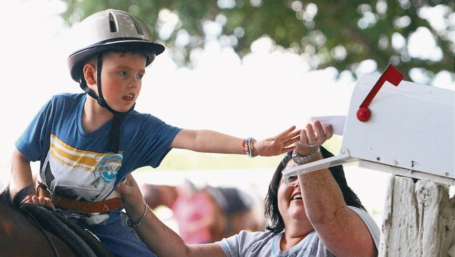 Ty Cox, 8, reaches to put an envelope into a mail box during a horse therapy session in El Paso's Upper Valley. Helping is occupatonal therapist Rachel Aguilar.