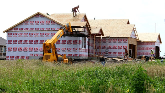 Workers build new homes in the North Gate residential community in Ankeny on Wednesday, July 9, 2014. There has been significant growth in the Ankeny community. It has hit the 50,000-resident mark. The growing population includes high numbers of construction for residential housing units.