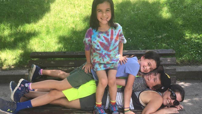 Parenting columnist Jamie Buss gets cozy on a park bench with her children (from top) Lucy, 7, Ella, 9, and Tyler, 13, during their scavenger hunt.