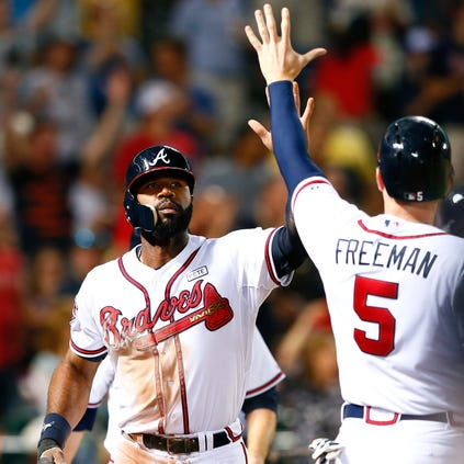 Jason Heyward #22 and Freddie Freeman #5 of the Atlanta Braves celebrate after scoring on a three-run single by Christian Bethancourt #25 in the sixth inning against the Washington Nationals at Turner Field on September 17, 2014 in Atlanta, Georgia.