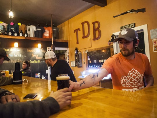 Michael Garrity, brewmaster, serves beer to a customer at Triple Dog Brewery in Havre. The brewery opened March 28, 2014, and brewers have created 27 flavors in-house, though they only serve eight on-tap at one time.