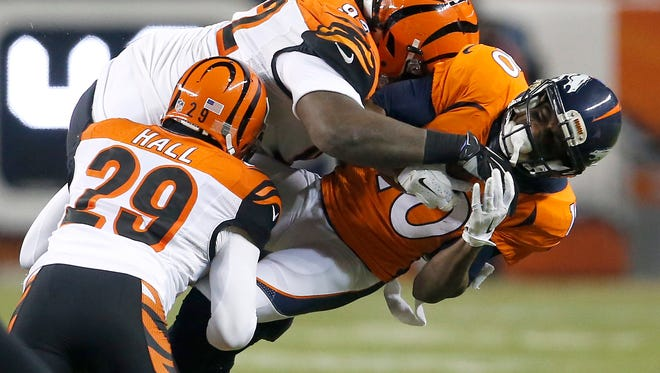 Bengals defenders Pat Sims and Leon Hall tackle Broncos wide receiver Emmanuel Sanders during a 2015 game.