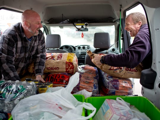 Marysville DPW employees Kraig Hohf and Jeff Gurley joke around as they deliver food to the SOS Marysville Food Pantry Tuesday, December 1, 2015 at 2929 Gratiot Boulevard.