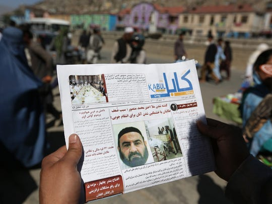 An Afghan man reads a local newspaper with a photo