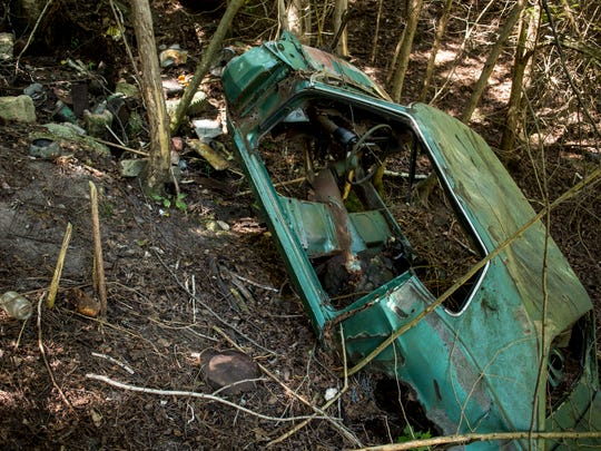 """The frame of an abandoned vehicle is seen on """"Glass Hill"""" Thursday, August 4, 2016 near the Black River and Hewitt Road in Grant Township."""