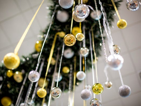 Ornaments hang from a large wreath on the ceiling as