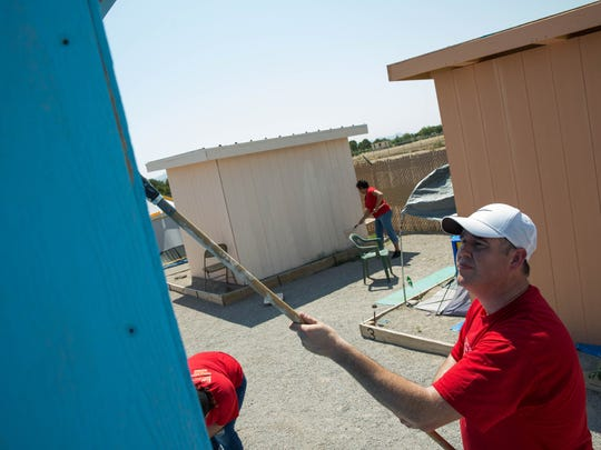 Brad Judy, the Keller Williams team leader and CEO of the company's Las Cruces and El Paso offices, paints the side of a tent shelter at Camp Hope, Thursday June 22, 2017. Keller Williams offices close once a year so that the employees can go out into the community and work on a project.