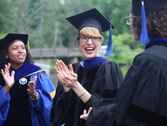 Vassar faculty member Lori Newman smiles as graduates pass her by on Sunday. Vassar conferred degrees to 586 graduating students.