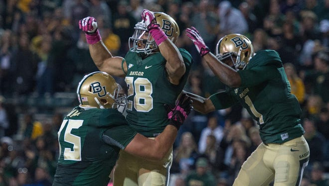Baylor offensive lineman Troy Baker (75), running back Devin Chafin (28) and wide receiver Corey Coleman (1) celebrate Chafin's touchdown against Iowa State during a 71-7 win Oct. 19 at Floyd Casey Stadium.
