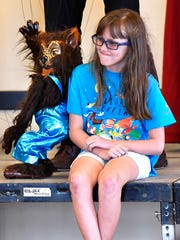 A young audience member tries not to laugh as a wolf marionette dances around her during Geppetto's Marionette Theater at the Children's Art & Literacy Festival Friday.