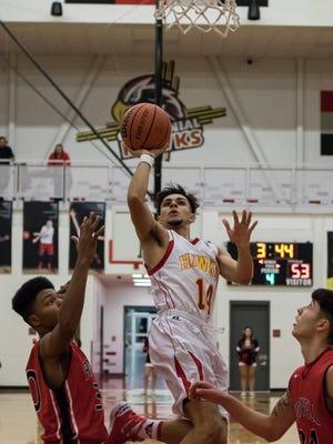 Centennial's Cesar Molina breaks through Roswell defenders for the basket.