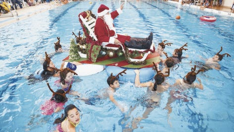 Children pull Santa Claus around the pool on Dec. 13, 2014, during a Christmas celebration at the Bloomfield Aquatic Center.