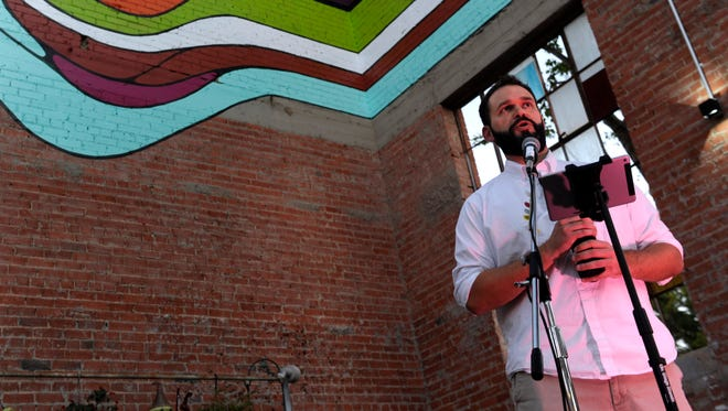 Artist Patrick Messersmith speaks at the opening of the SODA Courtyard on Nov. 2. The acronym South of Downtown Abilene and behind Messersmith is part of the mural he created for the space, which formerly was a Boy's Club building.