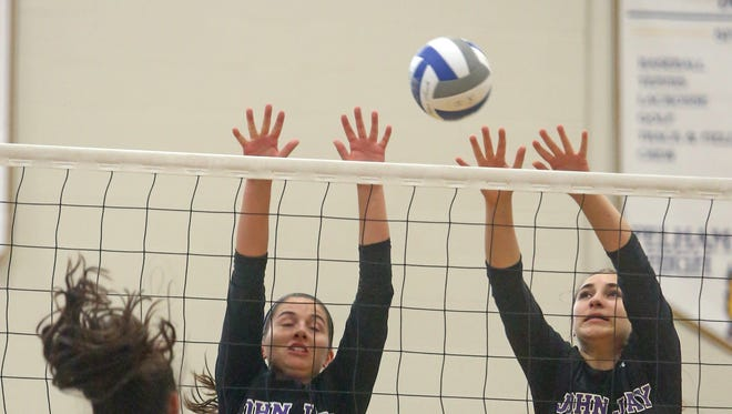 John Jay's Alex Hall and Rachel Cifarelli try to block a shot by Pelham's Kailee Chimento during a varsity volleyball match at Pelham High School Sept. 3, 2015.