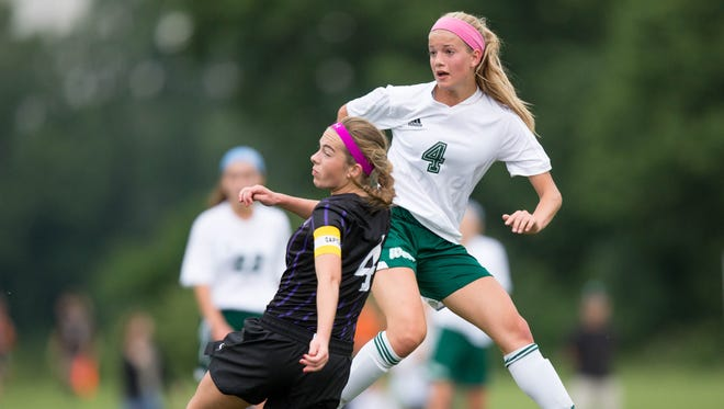 Iowa City West High School's Regan Steigleder kicks the ball past Waukee's Hannah McDevitt in the first half Thursday, June 11, 2015, during the IHSAA State Soccer Championships at Cownie Sports Complex in Des Moines.