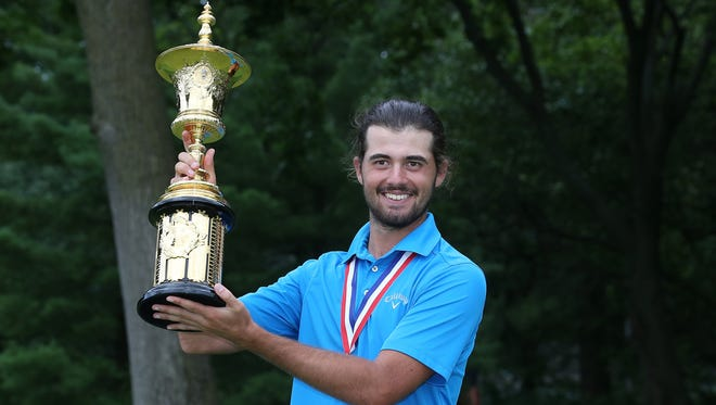 Curtis Luck celebrates with the Havemeyer Trophy after defeating Brad Dalke, 6-4, to win the U.S Amateur at Oakland Hills Country Club on Sunday.
