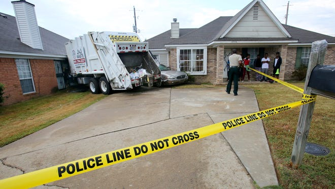 October 5, 2016 - As a safety precaution, a Shelby County Sheriff deputy stretches police tape around the scene of an accident on Cedargreen Cove where a garbage truck crashed into a house.