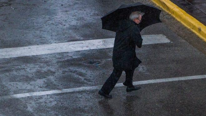 Pedestrians make their way through the downpour of rain in downtown Montgomery, Ala. on Wednesday November 30, 2016.