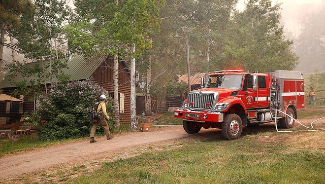 Firefighters patrol around a house west of U.S. Highway 550 near Hermosa, Colo., Friday, June 8, 2018. The firefighters were looking for spot fires as flames from the 416 Fire approached the homestead.