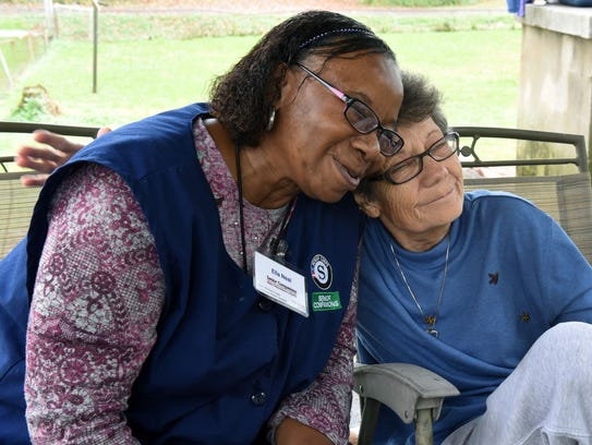 Mary, a 70-year-old deaf woman with dementia, hugs her Senior Companion, Ella Neal, left, during a visit Tuesday, Nov. 7, 2017. Neal helps Mary with light chores, but her primary purpose is to provide companionship for Mary, whose husband is in a nursing home.