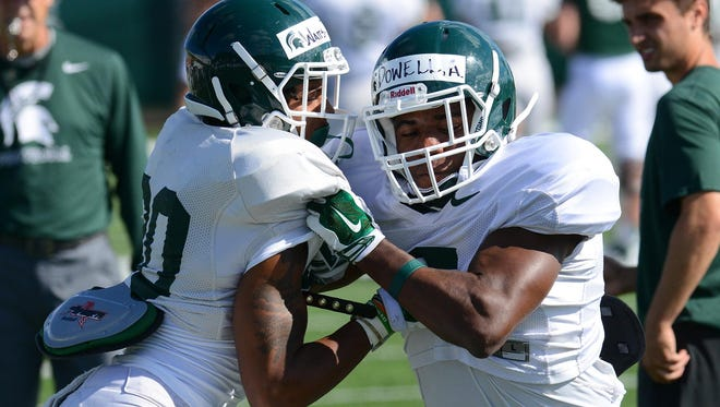 Spartan freshman linebacker Andrew Dowell (5) works to get around defensive back Jalen Watts-Jackson (20) Wednesday, August 12, 2015, during practice.