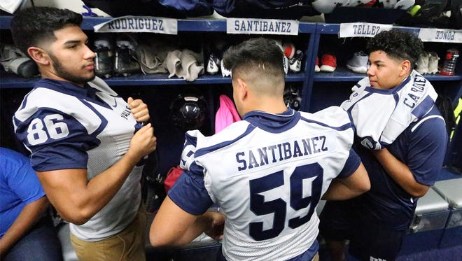 Del Valle High School football players Jorge Rodriguez, from left, Cristian Santibañez and Josias Cardiel try on new Nike jerseys in the team's locker room Wednesday. The players also received a Nike brand wind suit, compression shirt and polo shirt, said head coach Jessie Perales.