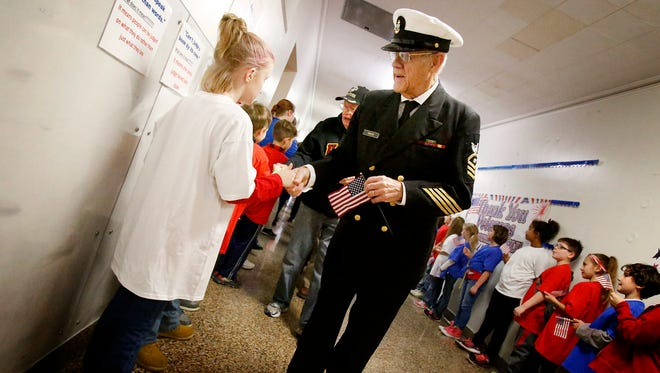Veteran Mahlon Parker, of Montour Falls, smiles as he shakes the hand of a Center Street Elementary student Friday as he makes his way down the hall. Parker served from 1958 to 1986 in the Navy as a chief boiler technician. Parker and more than 90 other veterans were honored at the elementary school one week before Veterans Day.