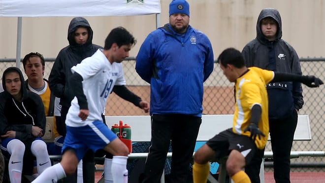 Olympic boys soccer coach Michael Wright watches from the sidelines during his team's game against Sequim on Tuesday. Wright said he's taking a defensive-minded approach to his first season leading the Trojans.