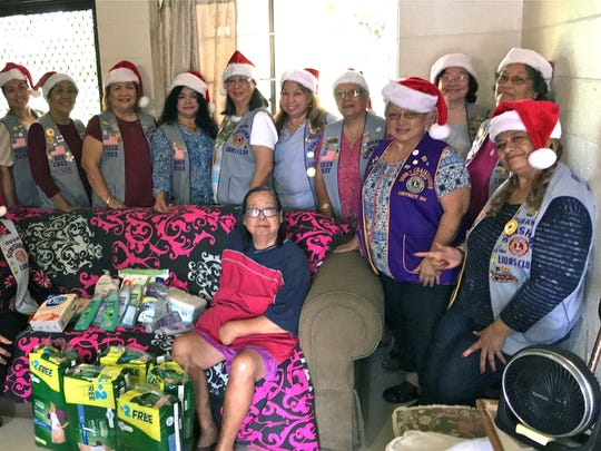 """In conjunction with the club's mission of """"Caring for the Sick and the Elderly,"""" Guam Sunshine Lions Clubs members brought supplies and toiletries for Frances Jesus, 69, at her residence in Mongmong on Dec. 9. The items were received by Martha Lizama, seated right, on her behalf. Club members are: Lion Marietta Camacho, seated left. Pictured standing from left: Lions Jill Pangelinan, Julie Garcia, Tish Tano, Dee Cruz, Julie Cruz, Connie Rivera, Annie Artero, Clarice Quichocho, Helen Colby, Ewy Taitano, Clare Cruz, Dot Leon Guerrero, and Lou Jean Borja."""