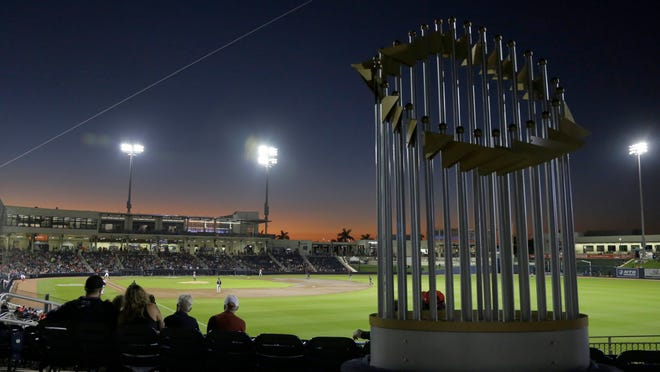 In this Feb. 27, 2020, file photo, a replica of the World Series trophy is seen in the stands as the Washington Nationals play the Houston Astros during a spring training baseball game Thursday, Feb. 27, 2020, in West Palm Beach, Fla. Major League Baseball has proposed expanding the playoff field from 10 teams to as many as 16 for this year and next season. Other major sports are accustomed to more teams in the postseason.