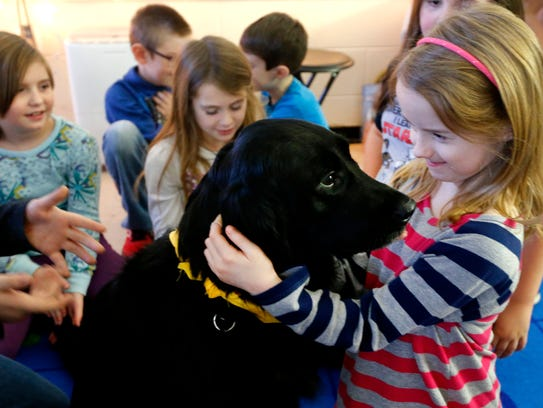 Christiana Elementary student Lynlee Tune pets Inca, teacher Paige Saylors' service dog, during class. Students know Inca is not working when she is not in her harness.