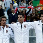 Portugal's Fabio Coentrao, Cristiano Ronaldo and Pepe, from left, sing the Portuguese national anthem prior a friendly soccer match between Portugal and Greece at the National stadium, in Oeiras, near Lisbon, Saturday, May 31, 2014. The game was a warm-up match for both teams ahead the World Cup in Brazil. The match ended in a 0-0 draw.