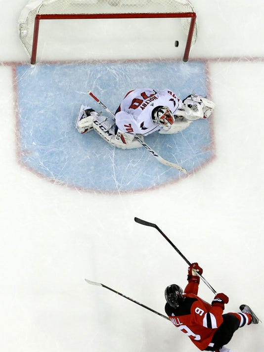 New Jersey Devils left wing Taylor Hall (9) scores on Washington Capitals goaltender Braden Holtby (70) during overtime of an NHL hockey game, Thursday, Jan. 18, 2018, in Newark, N.J. The Devils won 4-3. (AP Photo/Julio Cortez)