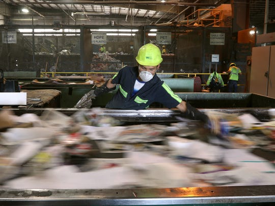 Employees pick contaminants off a conveyor belt in the paper sorting area at the Monroe County Recycling Center.