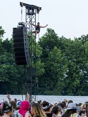 A fan scales the speaker tower as Snoop Dogg performs on The Lawn stage at Firefly in 2015.