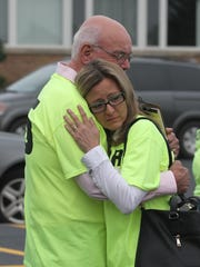 Angela and Steve Wesener hug outside the Edgar school building before they, supporters and friends attend the Edgar School Board meeting. The bullying-related suicide of the Weseners' son, Jonathan, and its aftermath was one of the topics considered by the board on Monday.