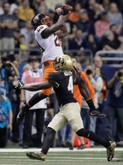 Oklahoma State wide receiver James Washington (28) makes a catch over Colorado defensive back Chidobe Awuzie (4) during the first half of the Alamo Bowl on Thursday, Dec. 29, 2016, in San Antonio.